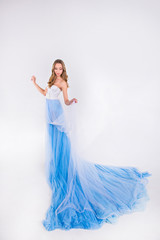 beautiful girl in a blue long dress with plume on a white backgr