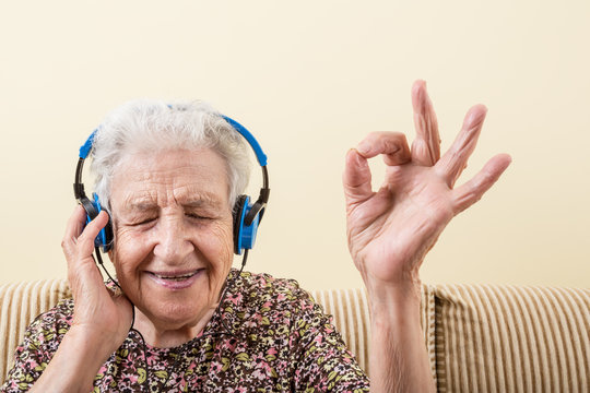 closeup of a lovely senior woman listening music with headphone