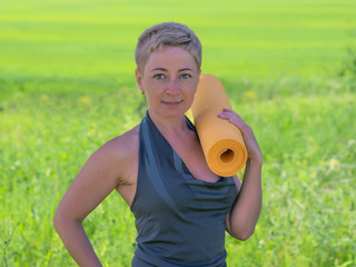 Mature Woman Holding Rolled Up Exercise Mat Outdoors