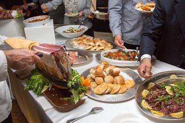 Taglio del prosciutto e persone che si servono al buffet