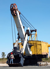 A child stands in the old excavator bucket without tracks