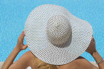 Lady with a straw hat looking at the swimming pool