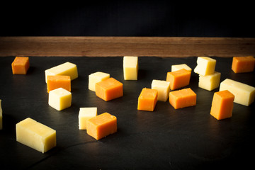 yellow and white cheddar cheese on a black background