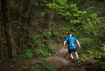 man with bag running on the trail down the steep hill in the green forest