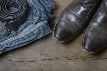 Jeans, Leather Boots and Belt on wooden Background