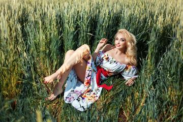 Beautiful girl on the field among ears of corn.