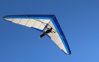 Hang Glider flying in the sky on a bright blue day