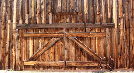 Wood Barn Doors – Front entrance of an old wooden farmhouse barn doors with metal wagon wheel