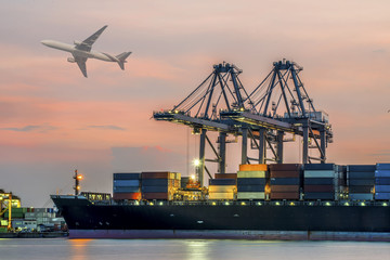 Fototapete - Container Cargo freight ship with working crane bridge in shipyard at dusk.