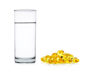 Water of glass with fish oil capsules isolated on the white back