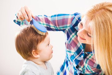 Mother brushing hair of her baby boy