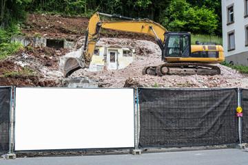 Leeres Schild am Bauzaun vor einer Baustelle mit Bagger