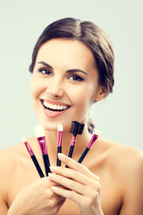 Young woman with cosmetics make up tools