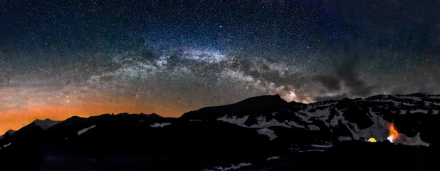 Camping in tent at night under Milky Way stars panorama