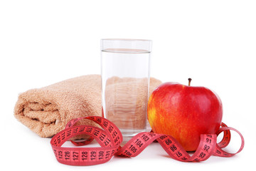 Red apple with measuring tape and glass of water isolated on white