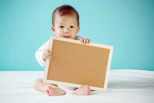 Infant child holding empty board, studio shot