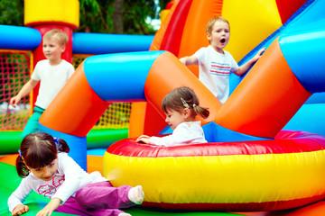 Fototapeta happy kids, having fun on inflatable attraction playground obraz