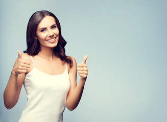 Portrait of happy woman showing thumb up gesture, with copyspace