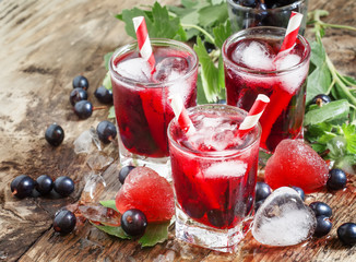 Fresh blackcurrant drink with berries and ice in a heart shape,