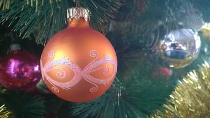 Fototapeta pomarańczowa bombka w białe wzory wśród innych na choince obraz