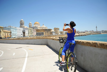 Woman biking taking a picture of the Cathedral of Cádiz, bike path, Andalusia, Spain