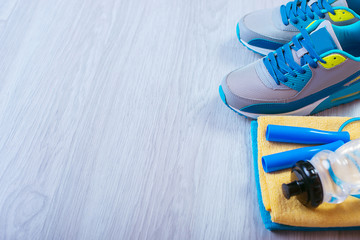 sneakers and a jump rope on a gray background.  Different tools for sport