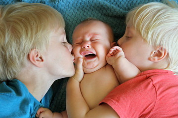 Young Brothers Kissing their Crying Newborn Baby Sister