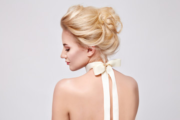 Beautiful gentle woman with silk bow on neck cosmetics body face