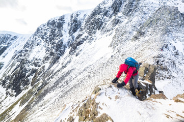 A climber ascending a snow covered ridge