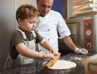 Boy learns to roll out  pizza dough
