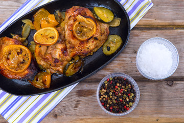 Delicious baked chicken thighs with lemon slices, onion and zucc