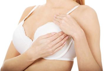 Woman examining breast in bra.