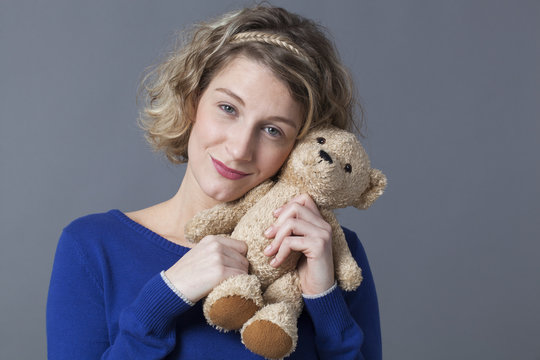happy young blonde woman hugging her teddy bear with tenderness for nostalgia