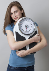 dieting young woman happy at her weight scale and silhouette