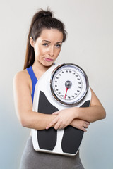 disappointed athletic young woman wearing sportswear holding big weighting scale with resignation