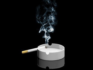 Cigarette and smoke on ashtray isolated on dark background