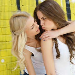 Two happy beautiful teen girls having fun outdoor against colore