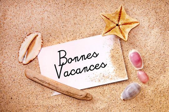 Bonnes vacances écrit sur une carte dans le sable et coquillages