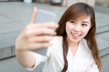 asian beautiful young woman using mobile phone to take selfie ou