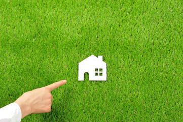 緑の芝生の上に置いてある白い家のシルエットと人間の手の仕草