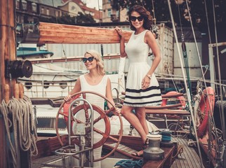 Stylish wealthy women on a luxury yacht