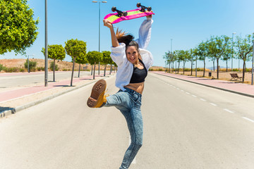 Happy young woman with her skateboard jumping on the road