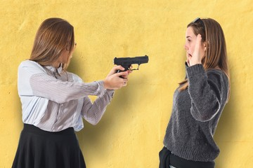 Teen girl pointing with a gun