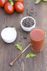 Tomato juice, tomatos, herbs and spices on wooden table