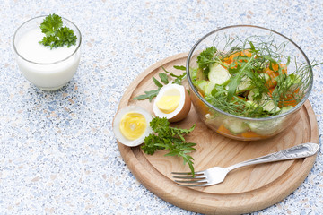 Salad with fresh vegetables and herbs in a glass bowl on a wooden board, boiled eggs and yogurt with herbs