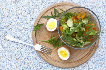 Salad with fresh vegetables and herbs in a glass bowl on a wooden board, boiled eggs