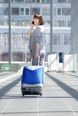 Traveling business woman walking with bag and mobile phone