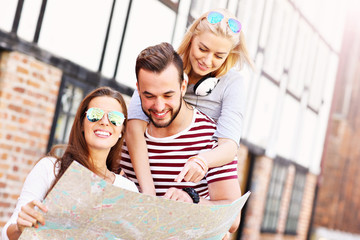 Group of happy friends sightseeing with map