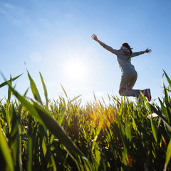woman jumping on grass meadow. Beautiful day outside.