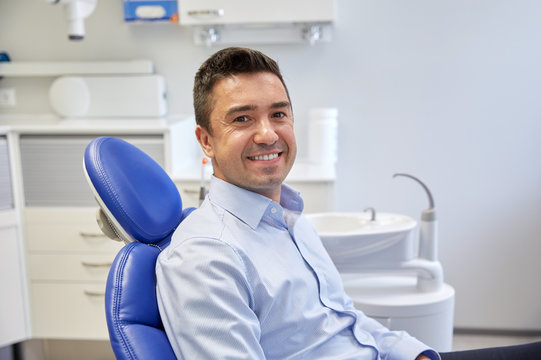 happy male patient sitting on dental chair